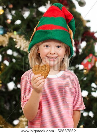 Smiling Elf Boy Holding Gingerbread Cookie