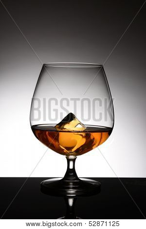 A brandy snifter with a single ice cube over a light to dark gray spot background. Vertical format.