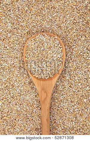 Pinhead oatmeal in a wooden spoon and forming a background.
