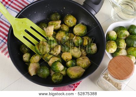 Fresh brussels sprouts in pan with vegetables and spices isolated on white