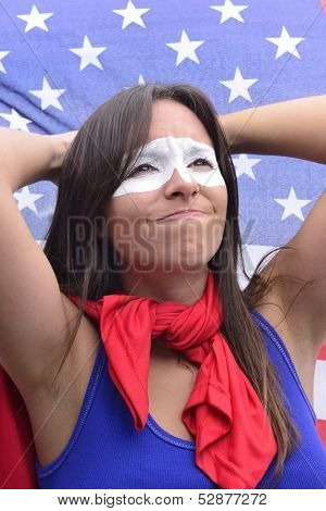 American woman Latin descent, disappointed with flag of United States of America in the background ground