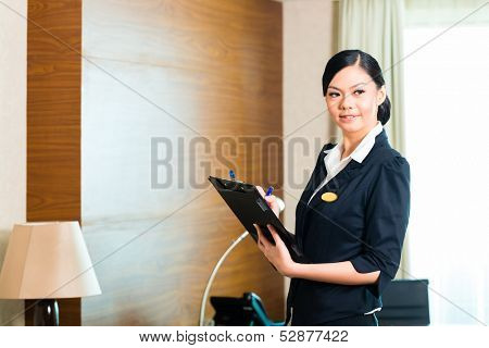 Asian Chinese Housekeeping manager or assistant controlling or checking the room or suit of a hotel with a checklist on tidiness