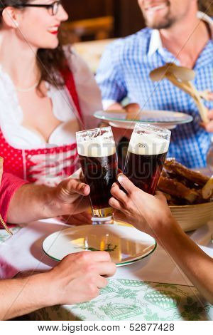 Young people in traditional Bavarian Tracht eating with sausages in restaurant or pub lunch or dinner