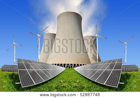 Solar energy panels before a nuclear power plant and wind turbines