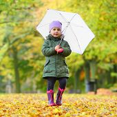 pic of rainy season  - Little girl with umbrella walking in the city park - JPG