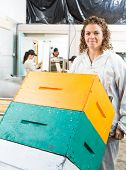 Portrait of female beekeeper holding trolley of stacked honeycomb crates in beekeeping factory
