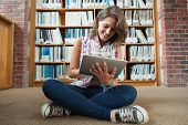 stock photo of short legs  - Full length of a happy female student against bookshelf using tablet PC on the library floor - JPG