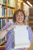 stock photo of librarian  - Happy female librarian holding a pile of books in a library smiling at camera - JPG