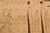 stock photo of horus  - relief on the facade of 1st pylon of the temple of Edfu with Pharaoh whipping the prisoners in front of Egyptian falcon god Horus - JPG