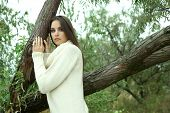 stock photo of pain-tree  - Portrait of young serious woman near tree - JPG