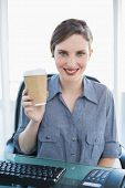 Cheerful young businesswoman presenting disposable cup sitting at her desk