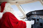 Man in Santa costume holding control wheel in cockpit of private jet