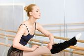stock photo of ballet barre  - Ballet dancer stretches herself near barre and mirrors in the dancing hall - JPG