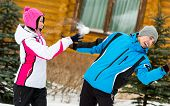 stock photo of snowball-fight  - Young couple having fun outdoors during winter vacations and playing at snowballs - JPG