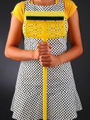 Closeup of a homemaker in an apron holding a sponge mop in front of her torso. Vertical format over