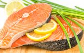 stock photo of salmon steak  - Salmon steak with lemon on a wooden board - JPG