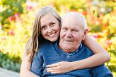 stock photo of retirement age  - Beautiful granddaughter visiting her elderly kind grandfather - JPG