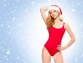 Beautiful, young and sexy Santa girl in Christmas swimsuit over winter background