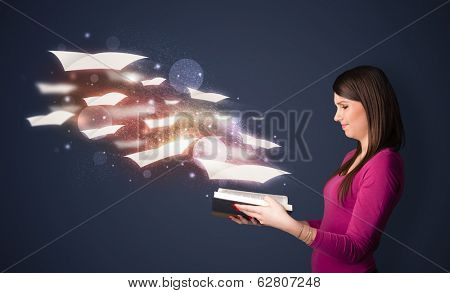 Young lady reading a book with flying sheets coming out of the book, magical reading concept