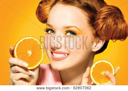Beauty Model Girl takes Juicy Oranges. Beautiful Joyful teen girl with freckles, funny red hairstyle and yellow makeup . Professional make up. Orange  Slices
