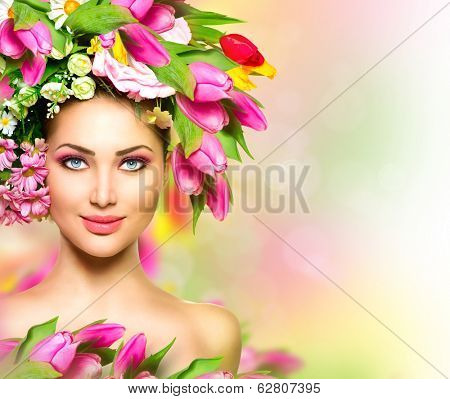 Beauty Summer Model Girl with colorful Flowers Hair Style. Spring Woman. Beautiful Lady with Blooming flowers on head. Nature Hairstyle. Holiday Creative Fashion Makeup. Make up. Blurred background