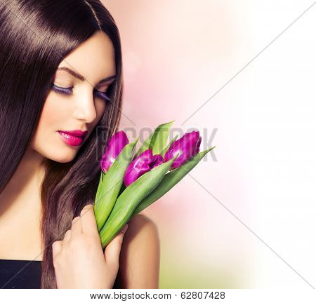 Beauty Woman with Spring Flower bouquet. Beautiful girl with tulips. Holiday makeup, celebration