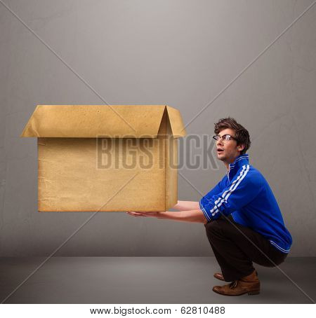 Goog-looking young man holding an empty brown cardboard box