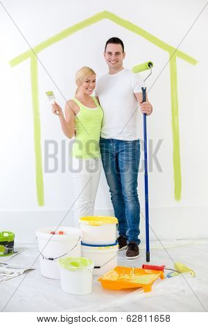 Happy couple painting their new home with panted home on wall in background