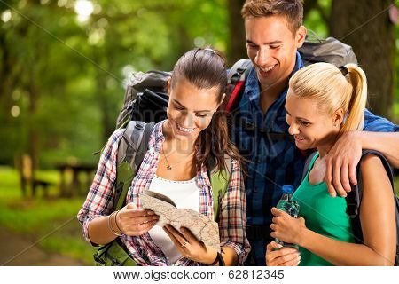 three young people together in a hiking, looking for directions from a map, feeling little lost