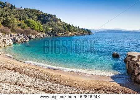 Tranquil Nissaki beach, a small cove lapped by limpid waters on the North-East coast of Corfu, Greece.