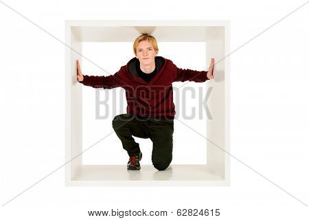 Young man in casual clothes sitting in white cube and listens. Concept of rules and restrictions. Isolated over white.