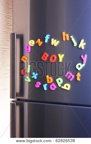 Word Boy spelled out using colorful magnetic letters on refrigerator