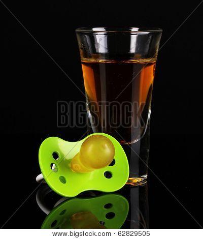 Baby dummy with alcoholic beverage isolated on black