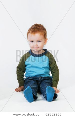 Redhead Little Boy Sitting On The Floor Smiling