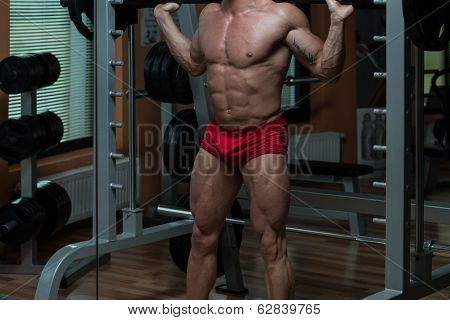 Young Man Performing Barbell Squats Exercise For Legs