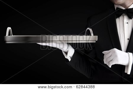 Waiter In Tuxedo Holding An Empty Tray Isolated On Black