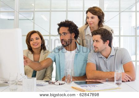 Group of young business people using computer together at office desk