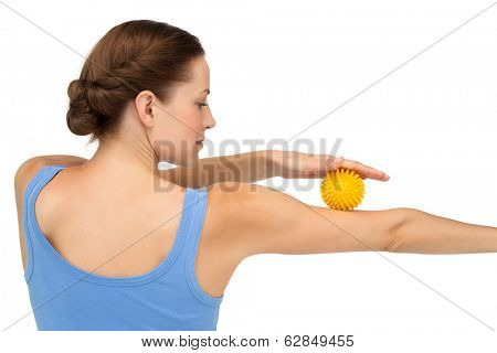 Rear view of a young woman holding stress ball on arm over white background