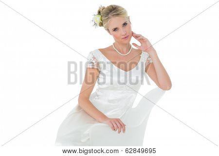 Portrait of sensuous bride sitting on chair over white background