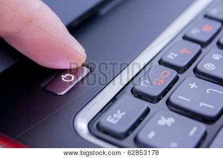 A Finger Is Pushing The Power Button To Wake Laptop Up