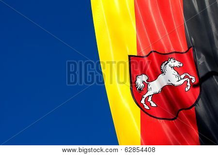 German Flag Of Lower Saxony Against The Blue Sky