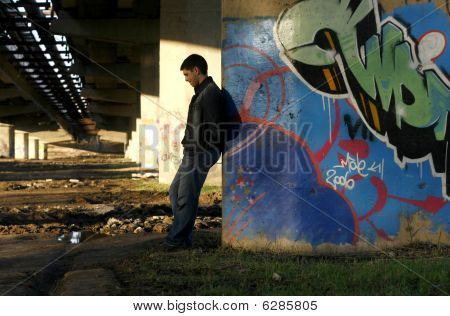 Young Handsome Man Leaning Against The Bridge Column With Colorful Graffit On It