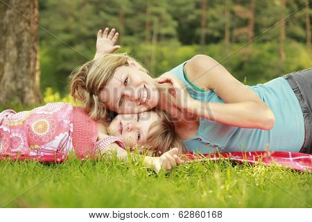 Mama And Her Little Daughter Lie On The Grass