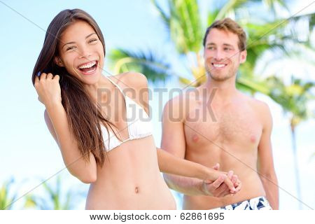 Couple fun at beach holding hands in bikini and swimwear smiling happy on honeymoon travel holidays in tropical paradise with palm trees. Happy interracial couple, Asian woman, Caucasian man.