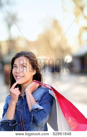 Shopping woman thinking looking up outdoors in fashion jeans jacket. Shopper girl holding shopping bags up on walking street. Mixed race Asian Caucasian female model La Rambla street Barcelona.