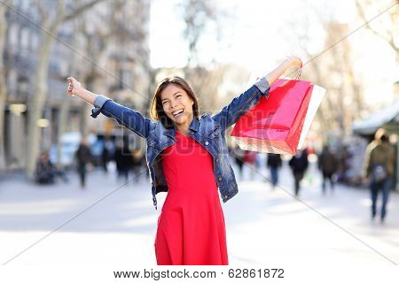 Shopping woman excited happy on La Rambla street in Barcelona. Shopper girl holding shopping bags up excited outdoors on walking street. Mixed race Asian Caucasian female model cheerful in Spain.