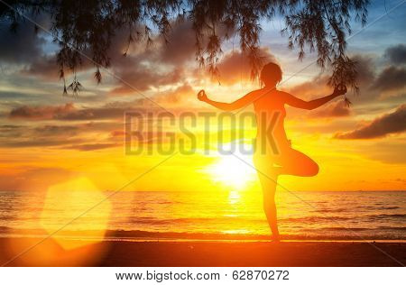 Yoga tree pose by woman silhouette with sunset sky background.