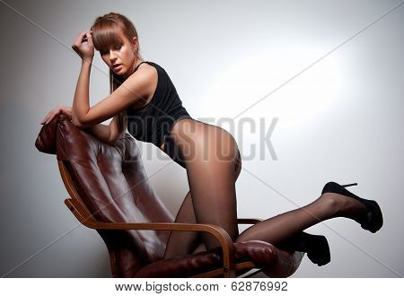 Attractive red hair model with black corset sitting provocatively on chair - gray background