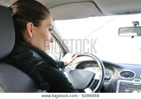 Portrait Of Young Smiling Woman Driving Car
