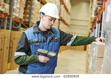 worker man in uniform scanning package in modern warehouse